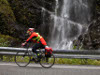 cyclist riding in front of a waterfall